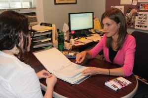 St. Thomas study abroad adviser Sarah Huesing talks with an Office of International Education student employee about course approval documents. Huesing helps students that decide to extend their stay to get courses approved. (Heidi Enninga/TommieMedia)