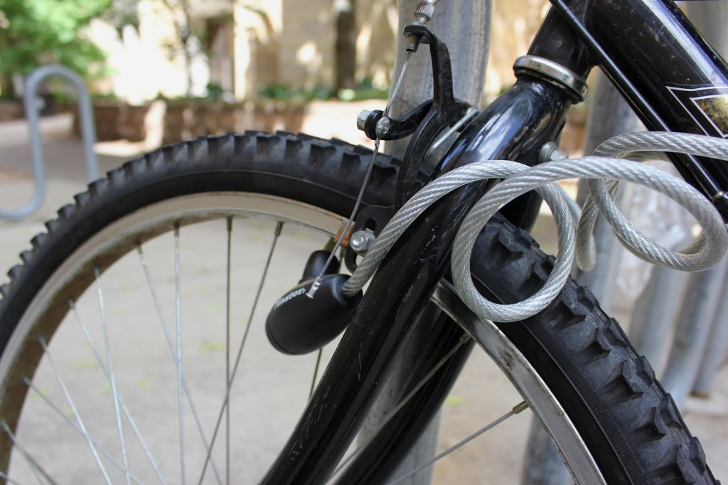 <p>A wire lock secures a bike on campus outside of the O'Shaughnessy Educational Center.  According to Public Safety, in May 2012 alone, 15 bikes were stolen on campus. (Hannah Anderson/TommieMedia)</p>