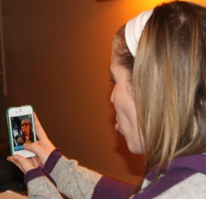 <p>Senior Hallie Lundell uses Snapchat to send a funny face photo to her friend. Lundell will not find her photo on Facebook later because the app permanently deletes the photo after it's viewed. (Laura Landvik/TommieMedia)</p>
