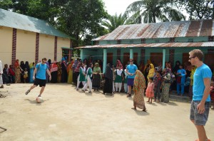 <p> Citizens of Bangladesh surround St. Thomas alumni Alex Daley (Left), Matt Scott (MIddle), and John Sunder (Right) as they kick the soccer ball around in a local village. While Sunder has no relation to Dribble Daily, he enjoys a fun game of soccer in efforts to promote community relations. The passion for soccer and extreme interest for creating clean areas for recreation sparked the idea to help out those who are less fortunate. (Photo courtesy of dribble daily.org)</p>