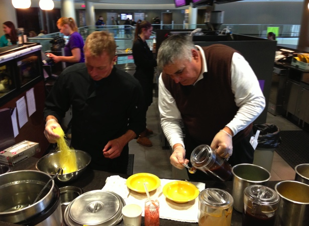 <p>Loft Supervisor Bruce Person and Ariake Representative Gary Ramsy prepare a bowl of ramen noodles. Person said the noodle bar was added to the Loft to drive students to the third floor of the Anderson Student Center. (Zachary Zumbusch/TommieMedia)</p>