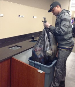 Senior Gauthier Mubwa picks up a bag of recyclables. (Kayla Bengtson/TommieMedia)