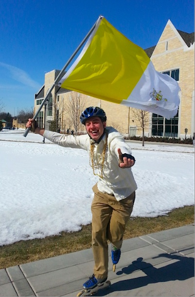 "<p>Junior seminarian Nathaniel Binversie celebrates in the Lower Quad at the sign of white smoke, yelling to others ""We have a pope!"" Binversie waved the Vatican flag while roller blading through the middle of campus. (Caroline Rode/TommieMedia)</p>"