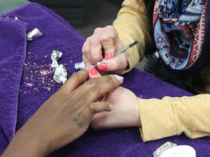 Stylist and nail technician Nicole Johnson gives junior Annette Wangongu a manicure at Estetica St. Thomas, the salon and day spa in the Anderson Student Center. Last month, the salon began offering a 30-minute Tommie manicure for $20 as part of its Beauty-on-a-Budget campaign. (Bjorn Saterbak/TommieMedia)