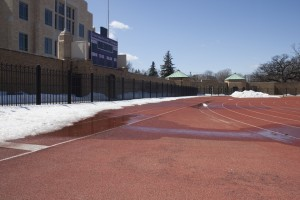 Snow piles remain lingering along the long jump runway at the south end of O'Shaughnessy Stadium. Spring sports teams, including the softball and baseball teams, may face several postponed games due to snow remaining on various MIAC athletic fields. (Jacob Sevening/TommieMedia)