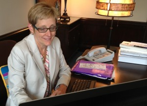 Julie Sullivan works at the president's desk in Aquinas Hall. (Heidi Enninga/TommieMedia)