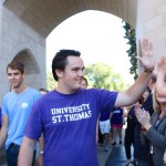 First-year Jack Jobst gives a high five to a child cheering him on as he walks through the arches. The class of 2020 had the largest amount of applications with lowest acceptance rate in St. Thomas history. (Natalie Hall/TommieMedia)