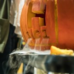 Chemistry club members put dry ice inside a carved pumpkin to create a spooky effect. Senior Grant Larson carved an H to represent the element hydrogen and included its molar mass of 1.01.  (Carlee Hackl/TommieMedia)