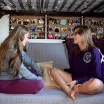 Freshmen Mac DeNicola and Alexis McHale sit on their futon and talk about what it's like to live in Dowling Hall.  The picture board behind them is composed of photos showing both girls' families, friends and experiences. (Miranda Lockner/TommieMedia)