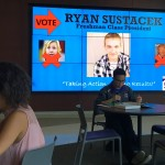 """Ryan Sustacek's politically-centered advertisement appears on a screen behind students studying in the Anderson Student Center. Sustacek won the election for freshman class president after running what he called a """"relevant"""" campaign. (Photo Credit: Ryan Sustacek)"""