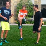 Juniors Zach Lang, Connor Theisen and friend Larry Martini stretch in the upper quad before a morning run. The St. Thomas group is collecting money for nonprofit World Vision by running in the Medtronic Twin Cities Marathon on Oct. 4. (Claire Noack/TommieMedia)