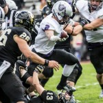 Running back Nick Waldvogel steps over a flattened St. Olaf defender during last year's game. The Tommies will go for their eighth straight win over St. Olaf Saturday. (Jake Remes/TommieMedia)