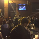A crowd congregates in front of a TV at Nomad World Pub to watch the first presidential debate on Monday. The pub event was hosted by MPR and featured games such as debate bingo. (Spencer Flaten/TommieMedia)