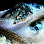 This undated photo provided by NASA and taken by an instrument aboard the agency's Mars Reconnaissance Orbiter shows dark, narrow, 100 meter-long streaks on the surface of Mars that scientists believe were caused by flowing streams of salty water. Researchers said Monday that the latest observations strongly support the longtime theory that salt water in liquid form flows down certain Martian slopes each summer. (NASA/JPL/University of Arizona via AP)