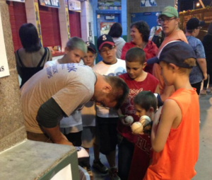 Dylan Thomas signs autographs for fans following one of his first games with the St. Paul Saints Minor League baseball team. Thomas signed with the Saints following a successful career as a pitcher on the St. Thomas baseball team. (Photo courtesy of Ashley Streitz)