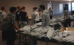 St. Thomas students try on sweatshirts to decide on sizes at the homecoming sweatshirt pickup on Sunday. This year, students were required to sign up for the Tommie Challenge in order to receive a sweatshirt. (Gabrielle Martinson/TommieMedia)