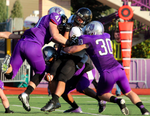 Tommie defenders crush a Ole running back in last year's meeting between these two teams. St. Thomas was victorious 35-21 at O'Shaughnessy Stadium in 2012. (Rosie Murphy/TommieMedia)