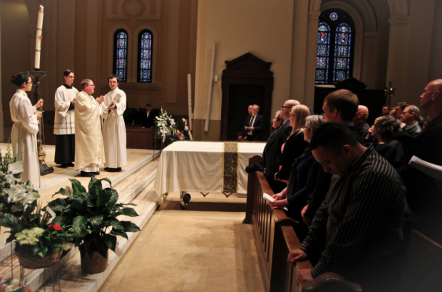 The Rev. Erich Rutten blesses the casket of theology professor Terence Nichols. Nichols died on April 12 at the age of 73 from cancer. (Eric Wuebben/TommieMedia)