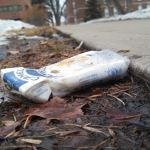 An empty cigarette carton lies next to the sidewalk entering campus. Some students are still smoking on campus despite a community-enforced smoking ban. (Simeon Lancaster/TommieMedia)