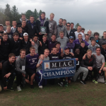 The St. Thomas men's track and field team pose with its MIAC championship banner. The championship is the Tommies' sixth in the past seven seasons (Tom Pitzen/TommieMedia).