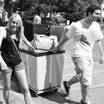 I pull one of two bins filled with dorm decor through the parking lot on freshman move-in day fall 2011 with a little help from a move-in volunteer. I've learned a lot since then and came up with a list to share with incoming freshmen. (Courtesy of Sandra Warfield)