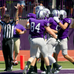 Tommies celebrate around running back Jack Kaiser after a 6-yard touchdown run. Kaiser had two touchdowns against the Blugold defense in the first half. (Jake Remes/TommieMedia)