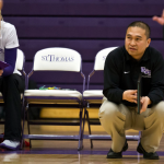 St. Thomas volleyball coach Thanh Pham crouches during last year's matchup against St. Mary's College. The team is looking to rebound after three early losses in its 2014 season. (Morgan Neu/TommieMedia)