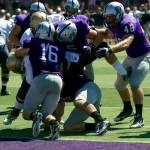 A swarm of Tommies make a goal line stand in their season-opener against Wisconsin Eau-Claire. Jim Rakow, St. Thomas head athletic trainer, said the training staff is confident in its focus on a new concussion program. (Jake Remes/TommieMedia)