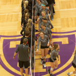 Members of the St. Thomas volleyball team clap hands with players from the St. Kate's team at the end of the match. The Tommies defeated the Wildcats 3-0 Wednesday night at Shoenecker Arena. (Madeleine Davidson/TommieMedia)