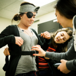 """St. Thomas graduates Megan Coffman and Grace Vo assist a student preparing to participate in the study. Using the """"Pirate Theory,"""" they recently conducted a study to better understand why people might be afraid of the dark. (Courtesy of Mark Brown/University Relations)"""