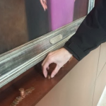 """Pennies are placed underneath the portrait of Lee and Penny Anderson in the Anderson Student Center. """"Lee and Pennyism"""" started out as a joke amongst a small group of friends last semester. (Whitney Oachs/TommieMedia)"""