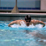 Freshman Bailey Biwer surfaces for a breathe during a race. Biwer was part of a MIAC champion men's swimming and diving team. (Madeleine Davidson/TommieMedia)