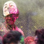 A man sits on someone's shoulders while wearing a Guy Fawkes mask and sprinkling green powder into the crowd. Holi's Festival of Colors celebrates the arrival and joys of spring with bright colors and vibrant music. (Carlee Hackl/TommieMedia)