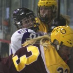 St. Thomas Forward Karina Marette crashes against the glass between two Cobbers. Marette is one of seven senior returning to the team. (Andrew Brinkmann/TommieMedia)
