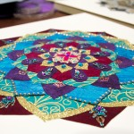 One of Broeker's mandalas sits on the table as inspiration for students creating their own. Mandalas have been used as contemplative and meditative objects in the Buddhist tradition for centuries. (Carlee Hackl/TommieMedia)
