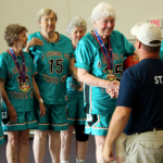 Clare Hanson is presented with a medal with her team from New Mexico, which won the women's basketball title for the over-80 age group. Hanson returned to basketball in 2000 after a 50-year break. (Elena Neuzil/TommieMedia)