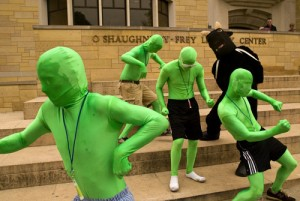 Four green men and someone in a bull costume dance on the steps of O'Shaughnessy-Frey Library. (Aaron Hays/TommieMedia)