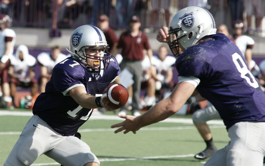 Quarterback Dakota Tracy hands the ball off to running back Ben Wartman. The Tommies ran the ball for a total of 330 yards and 6 touchdowns. (John Kruger/TommieMedia)