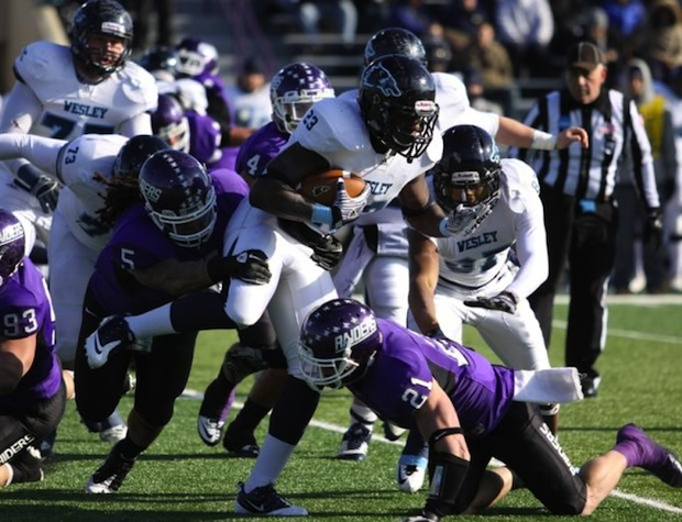 <p>Mount Union's Arthur Smith (5) and Mark Wood (21) converge on Wesley running back Askia Jahad in an NCAA Division III semifinal, Saturday in Alliance, Ohio. Mount Union's defense forced six turnovers to win 28-21. </p>