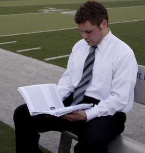 """Senior Shawn Zobel looks at a player profile in his """"2012 Draft Preview."""" Zobel just completed the book, which includes analysis of 255 college football players. (Heidi Enninga/TommieMedia)"""