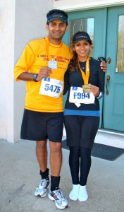 <p>Geena Maharaj poses with her father in front of her family's home after finishing the Twin Cities Marathon in 2010. It was her first marathon and her father's third. (Geena Maharaj/TommieMedia)</p>
