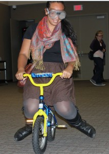 "<p>Senior Adaila Dixon attempts to ride a mini bicycle with alcohol impairment goggles on after Residence Life's ""Power Hour"" program. The goal of the presentation was to have a conversation with students about the dangers and effects of alcohol abuse. (Baihly Warfield/TommieMedia)</p>"