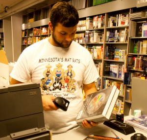 <p>Freshman Sam Larence scans books purchased by students at the St. Thomas book store. Textbooks are just one of the many factors that go into student loans. (Kayla Bengtson/TommieMedia)</p>