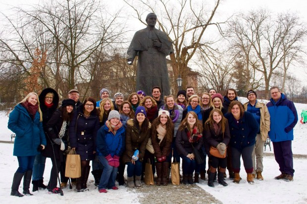 The class poses in front of a statue of St. John Paul II in Poland this past January. Media approached the group for interviews nearly every day. (Paul Wojda)