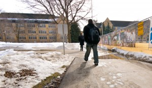 One student maneuvers around a puddle on a Lower Quad sidewalk. (John Kruger/TommieMedia)