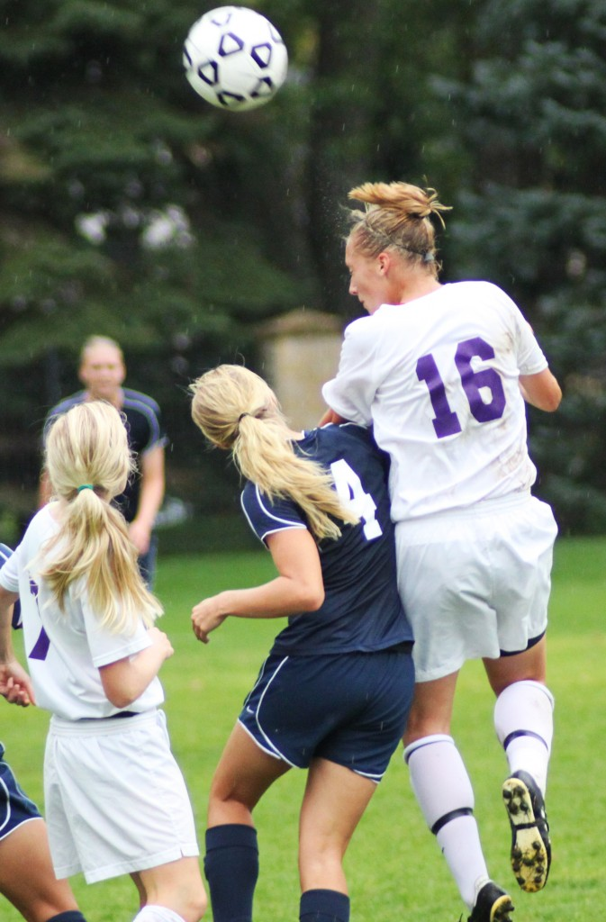 <p>Sophomore midfielder Anna Strehlow jumps higher than an Eau Claire defender to head the ball to a teammate. (Miles Trump/TommieMedia)</p>