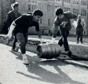 <p>Two students roll a keg down a campus sidewalk for the homecoming keg roll competition (Omar Marei/The Aquin)</p>