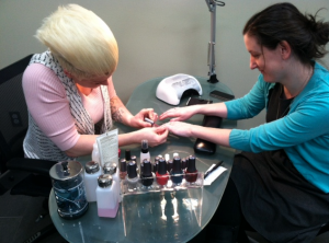 Stylist Amanda Christenson paints graduate student Sarah Snyder's nails at Madison & Co. Salon on campus. The salon opened April 1 and offers haircuts, styles and color along with waxing and nail services. (Michelle Doeden/TommieMedia)