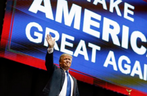 Republican presidential candidate, businessman Donald Trump waves has he arrives for a campaign rally Monday in Manchester, N.H. (AP Photo/David Goldman)