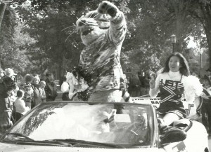 Cheerleader Sousada Chidthachack rides in the Grand Marshall car with Tommie the Tomcat in the 2002 Homecoming parade. (JOY LOMURRAY/THE AQUIN)